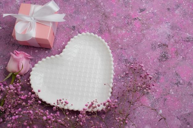 Piatto bianco con cuori su uno sfondo di fiori rosa e un regalo incartato. Foto Premium