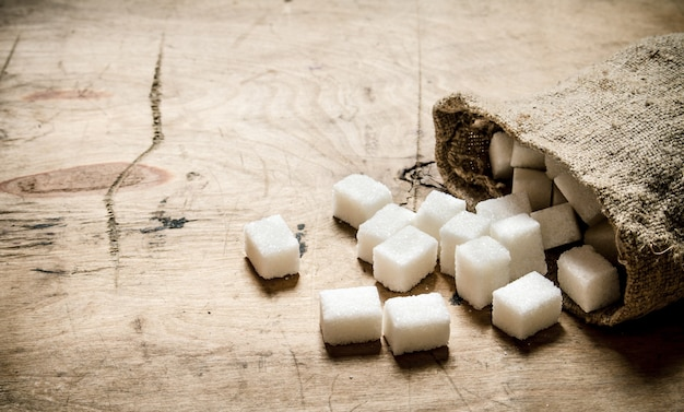 Zucchero bianco raffinato in borsa. sullo sfondo di legno. Foto Premium