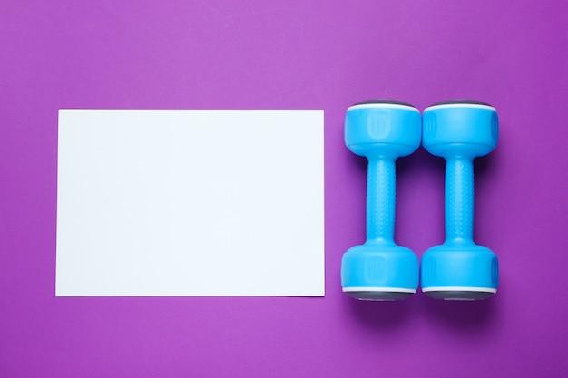 Foglio di carta bianco per lo spazio della copia, manubri di plastica sulla tavola porpora. tavolo fitness creativo Foto Premium
