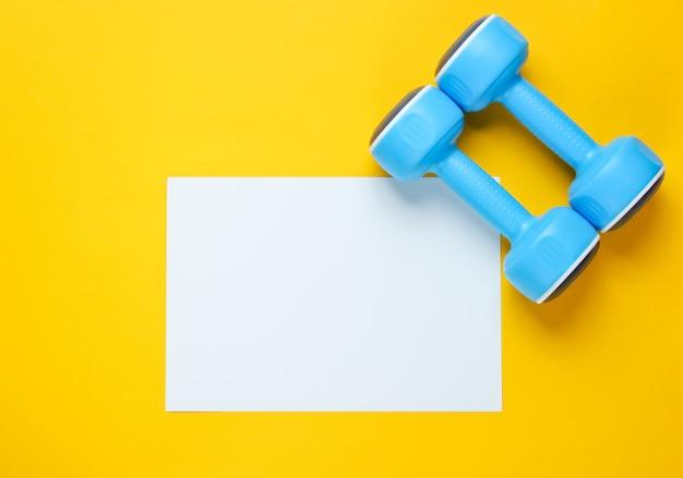 Foglio di carta bianco per lo spazio della copia, manubri di plastica sulla tavola gialla. tavolo fitness creativo Foto Premium