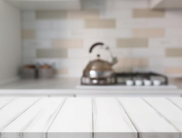 Superficie del tavolo bianco davanti al bancone della cucina a sfocatura Foto Premium