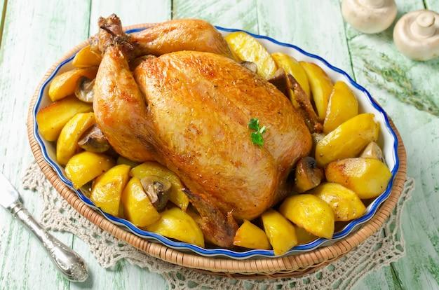 Pollo intero arrosto con patate e funghi Foto Premium
