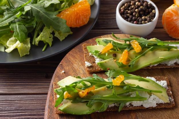 Pane croccante integrale con formaggio, avocado, foglie fresche e mandarino su fondo in legno Foto Premium