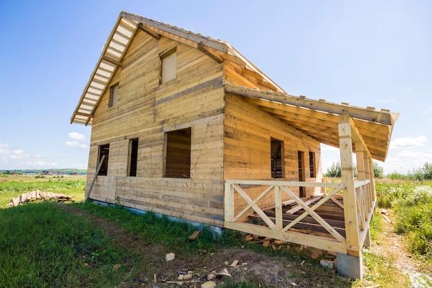 Vista grandangolare del cottage tradizionale ecologico di legno non finito dei materiali naturali del legname con il tetto ripido e il portico in costruzione in vicinanza verde sul fondo dello spazio della copia del cielo blu. Foto Premium