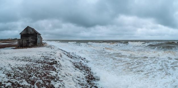 Ampia vista panoramica di un paesaggio marino spettacolare con un mare bianco impetuoso e una capanna di pescatori sulla riva Foto Premium