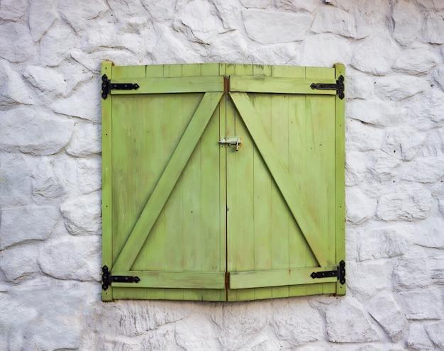Una finestra in legno e colore verde su una parete con texture di cemento bianco Foto Premium