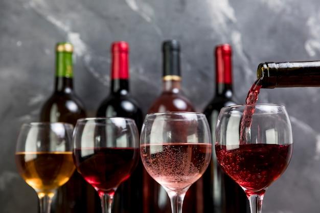Una bottiglia di vino che riempie wineglass Foto Premium