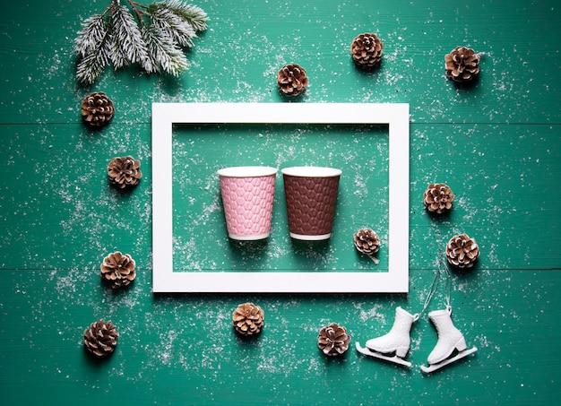 Inverno festivo concetto cornice coni rami di abete bicchieri di carta su uno sfondo di legno verde Foto Premium