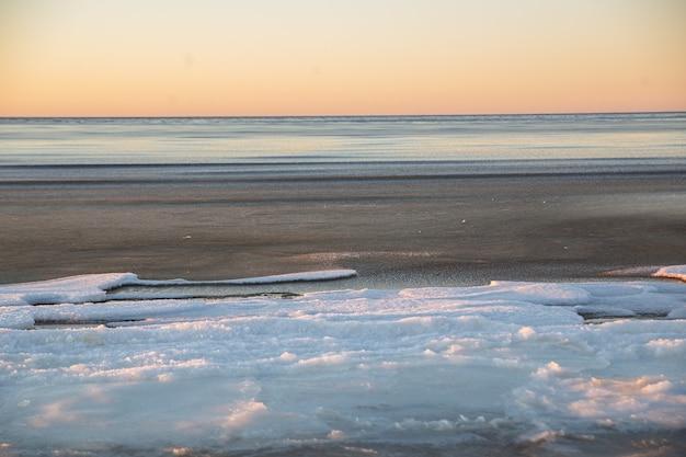 Paesaggio invernale in spiaggia, costa con ghiaccio incrinato e acqua di mare aperta. Foto Premium