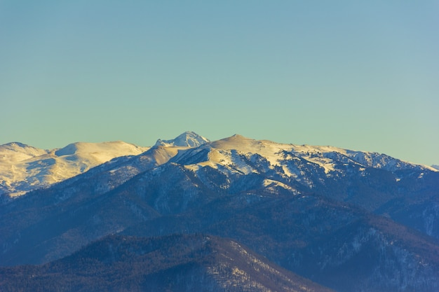 Paesaggio invernale con montagne e colline ricoperte di neve e sabbia dopo la tempesta di sabbia africana Foto Premium
