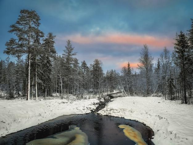 Il fiume di montagna invernale in carelia scorre attraverso la foresta Foto Premium