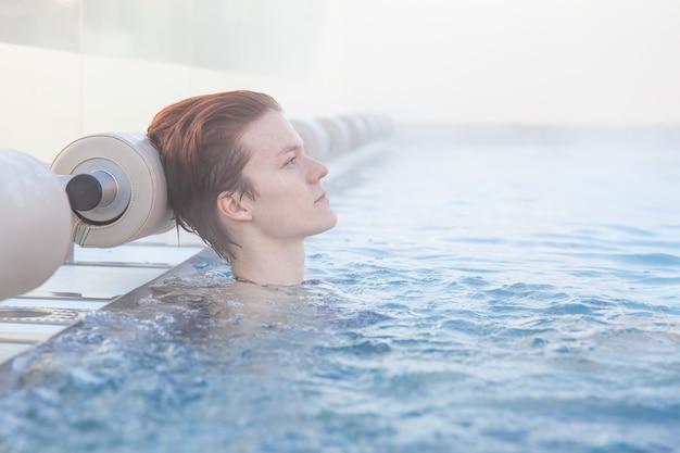 Piscina invernale con una giovane donna attraente e rilassante. Foto Premium