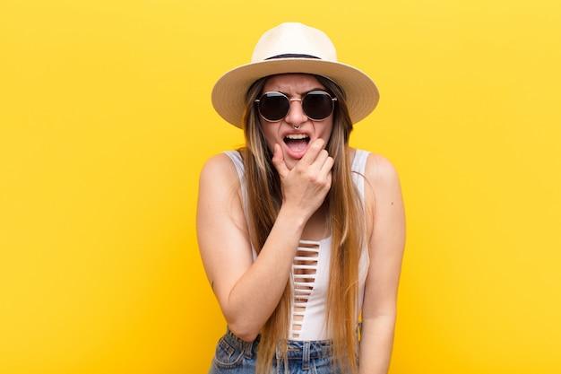 Con la bocca e gli occhi spalancati e la mano sul mento, sentirsi spiacevolmente scioccati, dire cosa o wow Foto Premium