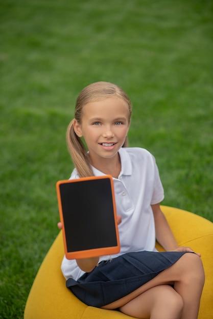 Con tablet. studentessa bionda carina seduta su una sedia borsa e mostrando il suo tablet Foto Premium