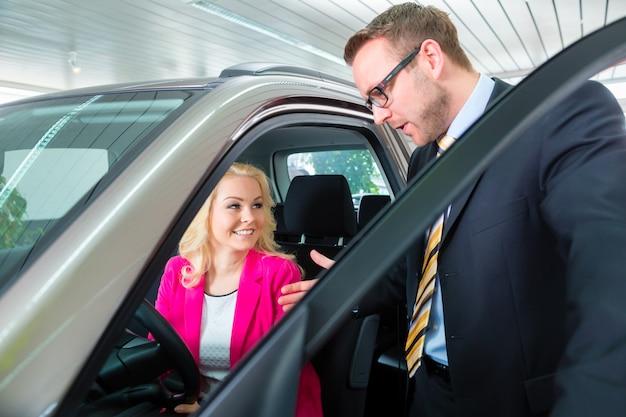 Donna che compra nuova automobile nel concessionario auto Foto Premium