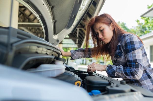 Donna che controlla il livello dell'olio in un'auto Foto Premium