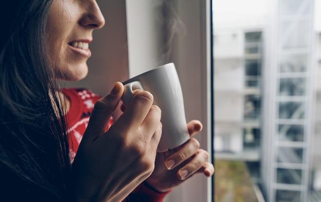 Donna in un maglione di natale che tiene una tazza vicino alla finestra Foto Premium