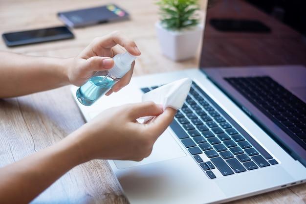 Donna che pulisce laptop e smartphone con salviettine umidificate e disinfettante per alcol sul posto di lavoro durante il lavoro a casa, protezione da coronavirus (covid-19) infezione. Foto Premium