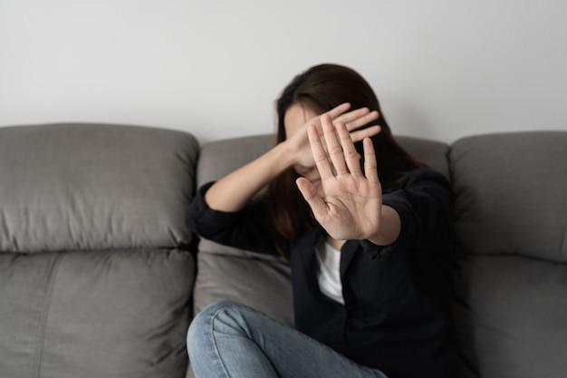 Donna che copre il viso per paura di violenza domestica, violenza di concetto e abusi. Foto Premium
