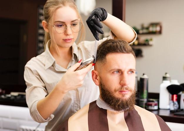 Donna che taglia i capelli del suo cliente   Foto Premium