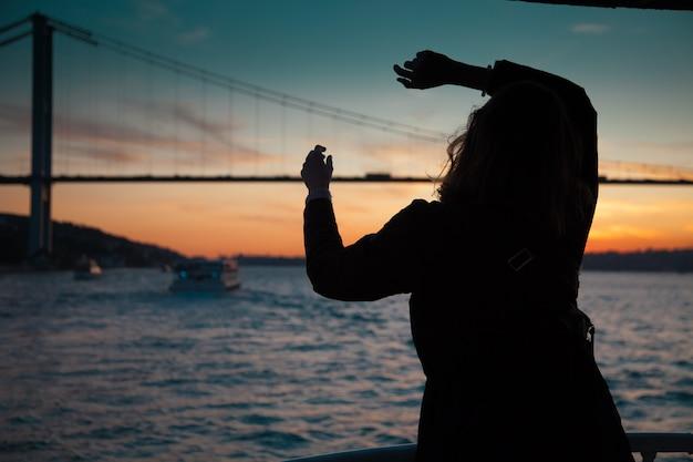 Donna in cappotto scuro in piedi con le mani in alto sul ponte di osservazione nel traghetto Foto Premium