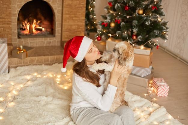 Donna e cane che si divertono a natale, seduti sul pavimento su un morbido carper, la signora vuole baciare il suo cane, in posa nell'accogliente soggiorno con albero di natale e camino, cappello da babbo natale. Foto Premium