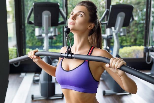 Donna che fa esercizio per lei indietro - pulldown del lat Foto Premium