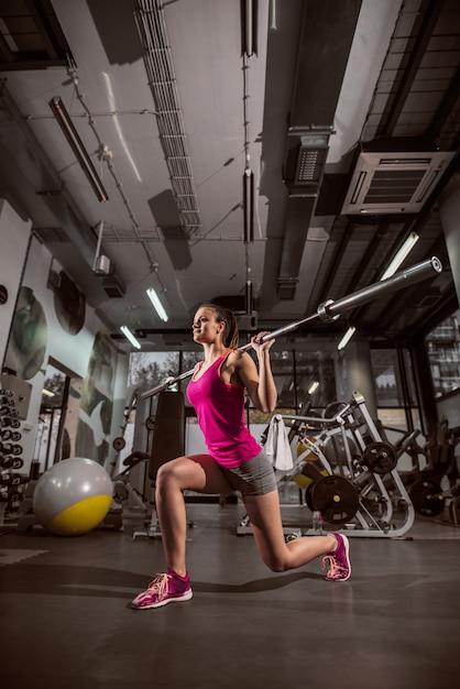 Donna che fa gli esercizi con la barra del peso in una palestra. Foto Premium