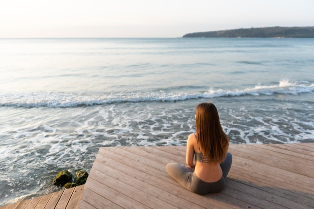 Donna che fa yoga vicino al mare Foto Premium