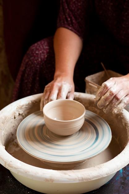 Donna in abito da modellare in argilla su un tornio da vasaio Foto Premium