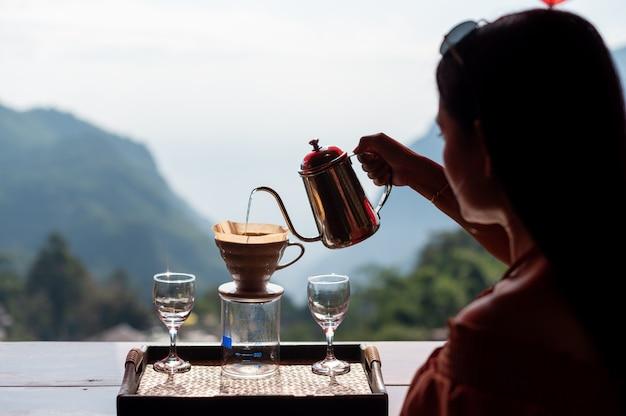 Donna che gocciola il caffè al villaggio di phahee, chiang rai, thailandia Foto Premium