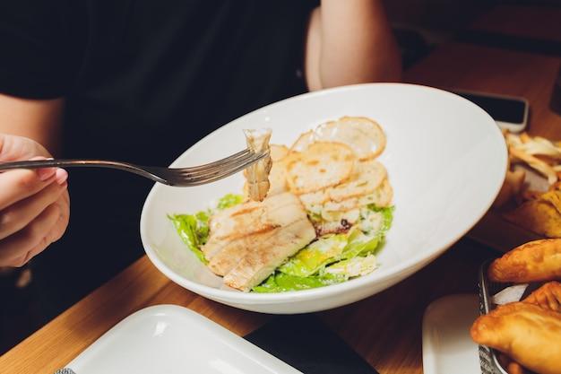 Donna che mangia pesce da asporto britannico tradizionale e patatine fritte con salsa di pomodoro. Foto Premium