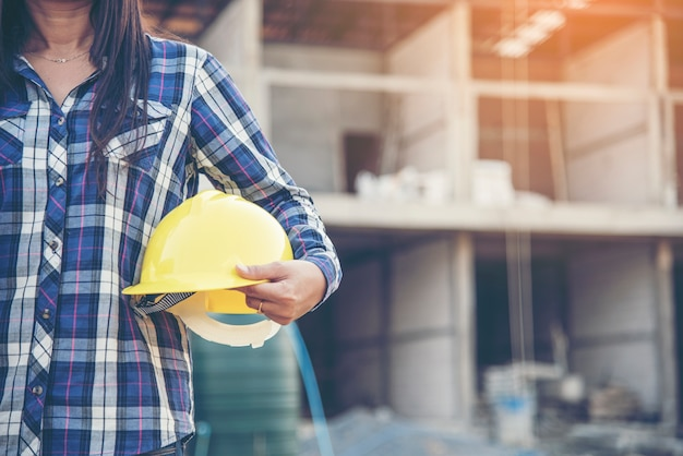 Ingegnere della donna che lavora sul cantiere e che tiene la protezione della testa del casco di sicurezza del cappello duro giallo all'industria manifatturiera. concetto di costruzione. Foto Premium