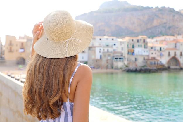 Donna che gode della vista della città vecchia di cefalù in sicilia, italia Foto Premium