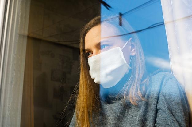 Una donna con una maschera di garza guarda attraverso la finestra Foto Premium