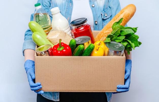 Donna in guanti che tengono le forniture alimentari della scatola di donazione per la gente in isolamento. prodotti essenziali: olio, conserve, cereali, latte, verdure, frutta Foto Premium