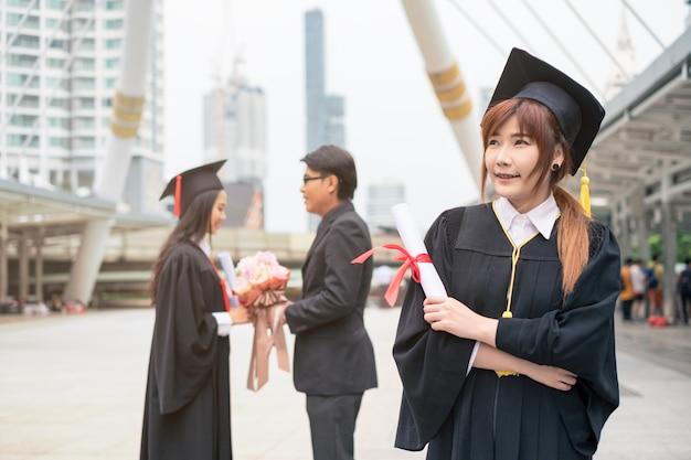 Diploma di laurea laureato della holding della donna con congratulazioni di coppia Foto Premium