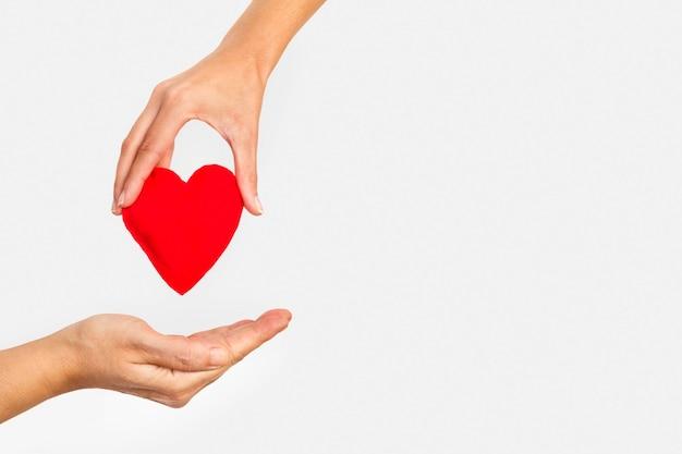 Mano della donna che dà un cuore rosso a una mano dell'uomo su una priorità bassa bianca con lo spazio della copia Foto Premium
