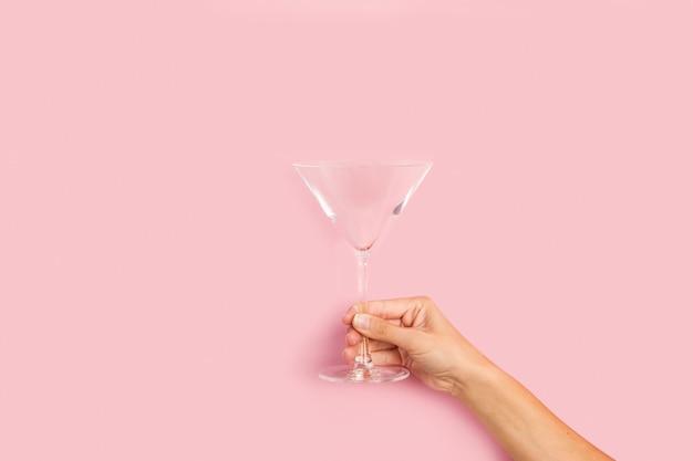 Mano della donna che tiene un bicchiere da cocktail su uno sfondo rosa Foto Premium