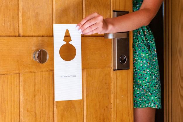 La mano della donna che tiene e appende l'insegna non disturba sulla porta in hotel Foto Premium