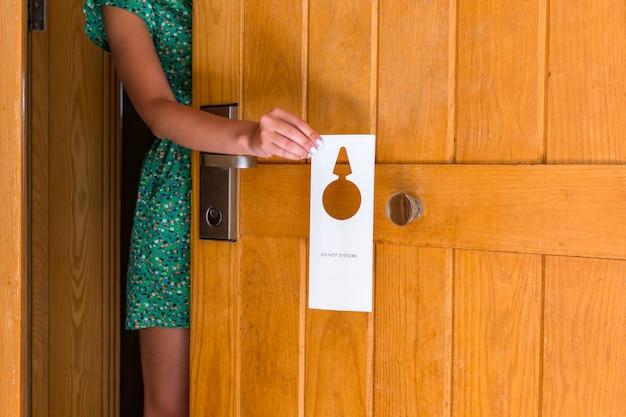 La tenuta della mano della donna e l'insegna appende non disturbano sulla porta in hotel Foto Premium