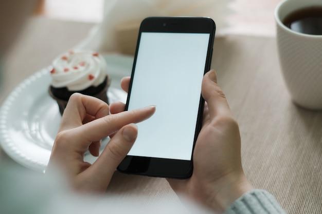Mano della donna che tiene il telefono cellulare, usando in applicazioni mobili e programmi multimediali. Foto Premium