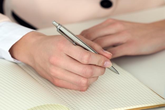 Mano della donna che tiene la penna d'argento pronta a prendere nota nel taccuino aperto. imprenditrice o dipendente sul posto di lavoro scrivendo idee di business, piani, attività all'organizzatore personale. Foto Premium