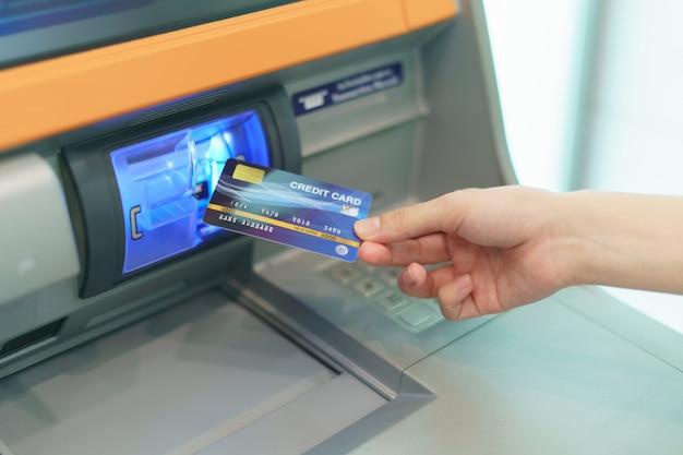 Mano della donna inserendo una carta di credito, nel bancomat per prelevare denaro presso il bancomat. Foto Premium