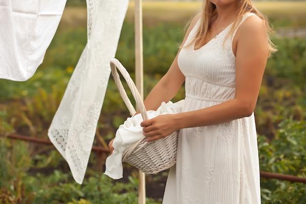 Donna mano lavaggio e appendere il bucato all'aperto in una giornata di sole. donna che tiene un secchio di latta d'acqua. stile retrò. Foto Premium