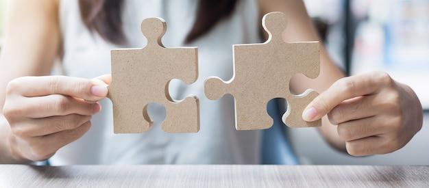Le mani della donna che collegano le coppie puzzle sopra la tavola, donna di affari che tiene il puzzle di legno dentro l'ufficio. soluzioni aziendali, missione, target, successo, obiettivi e concetti di strategia Foto Premium