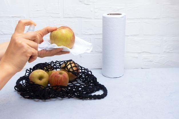 La donna passa la tenuta del prodotto disinfettante e la pulizia delle drogherie in cucina con la borsa della maglia sulla tavola Foto Premium