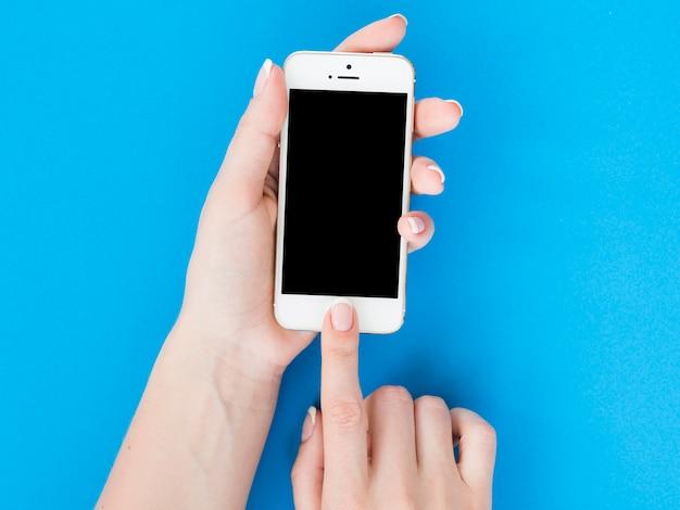 La donna passa lo smartphone della tenuta su fondo blu Foto Premium