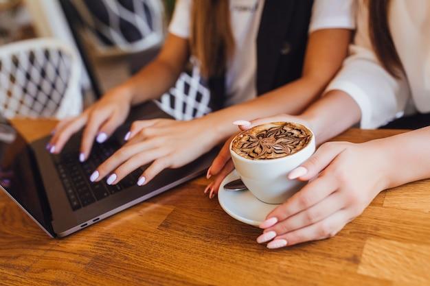 Mani della donna con latte durante il lavoro in ufficio Foto Premium