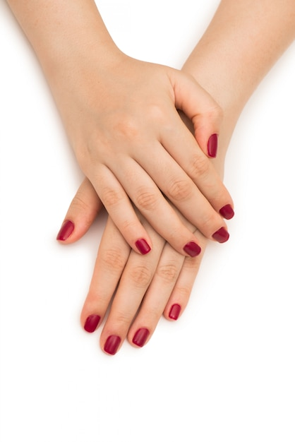 Mani della donna con l'unghia rossa isolata su bianco Foto Premium